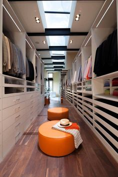 awesome closet layout and the mirror adds to much visual depth and who could resist the pop of orange seating!