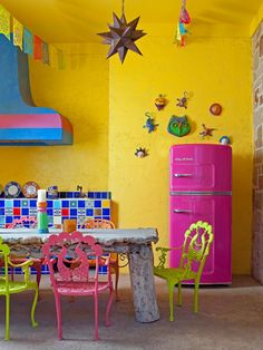 A friendly hot pink refrigerator by Big Chill and lots of bright hues bring a modern touch to this outdoor, Mediterranean-inspired kitchen.