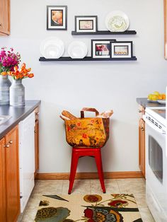 Notice that generic cabinetry, flooring, and appliances come alive with bold pops of color in the rug, stool, shopping bag, and art.  Even the flowers and fruit add to the decor.