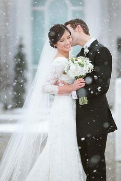 Kiss on a snowy wedding day.