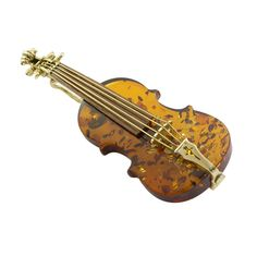 A gold and amber violin brooch