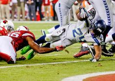Seattle Seahawks running back Marshawn Lynch (24) falls into the end zone for a touchdown as Arizona Cardinals inside linebacker Karlos Dansby (56) defends. (Ross D. Franklin/AP)