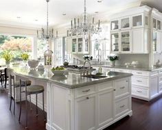 Beautiful Gourmet Kitchen. While glossy cabinets. Crystal chandeliers. Modern kitchen design.