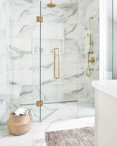 gold Bathroom Decor Luxurious white and gray marble shower with a white niche enclosed with glass doors and brass hardware.