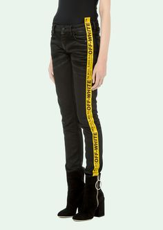"""Skinny Levi's in black.5 pockets styling. Yellow industrial stripes at side legs.  Model: Victoria wears size 27 Height: 177 cm - 5' 9.5"""" Waist: 59 cm - 23"""" Hips: 87 cm - 34"""""""