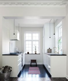 Classic modern kitchen with black floor, white cabinets and black counter