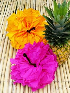 """They are sooo easy to make - Just make a paper pom like you would normally (tutorial here), then twist a piece of brown pipe cleaner around the center of each open pom, and open the pom flat, scrunching some of the """"petals"""" to give it the Hibiscus look."""
