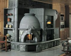 This particular soapstone fireplace not only warms the house but you can also bake and cook in its bakeoven (on the right).