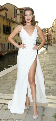 Old school glamour: Bella Hadid, 20, went for pure Italian bombshell in her plunging icy white dress which flashed her ample cleavage and, thanks to the thigh-high split, a generous glimpse of her toned pin at the Bulgari bash in Venice on Friday