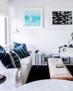 Coastal-inspired living room with beachy art, neutral sofa and blue pillows