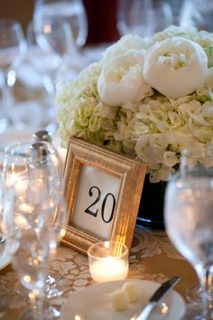 Wedding Table Decor: Gold & White. Picture frames for table placement.... love that idea that doubles into a gift for the guests.