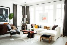 Sophisticated living room with hide rug, linen sectional, and modern artwork via @thouswellblog