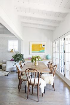 White ceilings, great art, rustic table and bentwood chairs…love it all! Brittany Ambridge | Domino Magazine