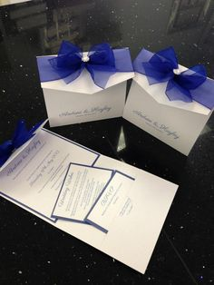 Royal blue and ice white pocketfold style invitation with big organza bow and pretty jewel