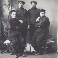 Twee Scheveningse en twee Urker vissers (zittend), gekleed in de voor hun plaats typerende truien.