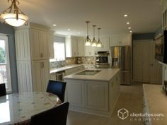 Classic white kitchen remodel with Cambridge Painted White raised panel kitchen cabinets from CliqStudios. A coffee bar, flat stove top, double oven, multi-color subway tile backsplash, and pendant lighting complete this storage friendly upgrade.