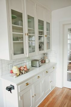 From the Nato's: original built-ins are given new life with a fresh coat of paint, brass hardware and a subway-tile backsplash.