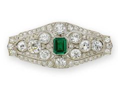 An art deco diamond and paste brooch, circa 1920  The pierced plaque millegrain-set throughout with old brilliant-cut diamonds of various sizes, the largest in collet settings, surrounding a central step-cut green paste, principal diamonds approximately 6.25 carats total, remaining diamonds approximately 1.80 carats total, green paste a later replacement, length 5.6cm.