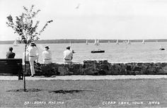 "Clear Lake, Iowa. View from the city park sea wall built by the WPA during the 1930s. The Oakwood Park neighborhood is the opposite shore. That elm tree was replaced in the 1980s, and the ""new"" trees are quite a bit larger than the one pictured here."