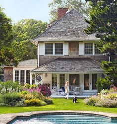 A shingle style cottage in the Hamptons features a back porch that overlooks a beautiful garden and pool. - Traditional Home ® / Photo: Francesco Lagnese