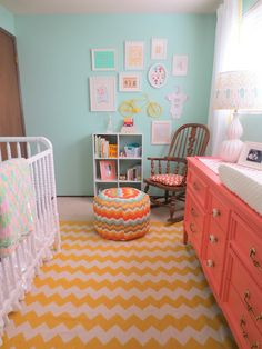 Colorful baby girl nursery / Yellow chevron rug / Aqua feature wall / Coral dresser and changing table