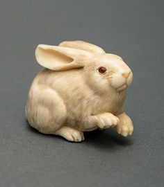 Netsuke. Ivory and Horn. Japan, approx. 1975 HEIGHT 3,2 CM The work of a modern master born 1931 in Tokyo. According to legend, the rabbit turns snow white after 1000 years of age. The eyes are two-colored inlaid horn and very lively in expression. Himotoshi on bottom and signature BAI-SHODO YASU-FUSA on legs. The name Baishodo comes from the studio, the artist´s real name is Saito Yasufusa. From a private German collection