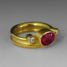 Oval Rubelite and diamonds by Barbara Heinrich || An 18k yellow gold, offset ring with an oval rubelite1.73cttw and 2 side diamonds=.16cttw. Ring $1,960.00