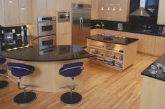 Modern kitchen with a big curve by BeckySue Becker, CKD, CBD, CAPS.   Natural maple slab doors, absolute black granite tops, KitchenAid appliances