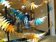 colored tissue covered wire clothes hangers made the garlands hanging in the window display