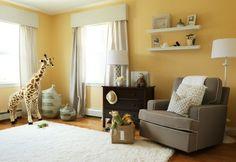 peintrue chambre bébé ocre, canapé gris, étagères murales, tapis blanc, commode en bois massif, sac à jouets