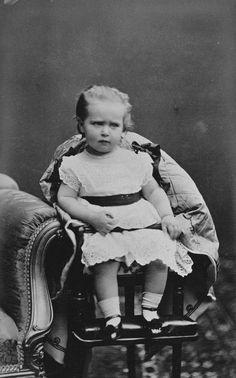 A jovem princesa Alix de Hesse está sentada em uma cadeira alta. Ela usa vestido de mangas curtas, meias curtas, sapatos. Dezembro de 1873.