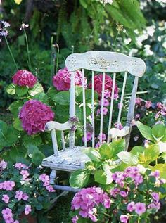 A lovely romantic painted rocker!!! Bebe'!!! Amidst a cottage garden of pink hydrangea, blooming host as and periwinkles!!!