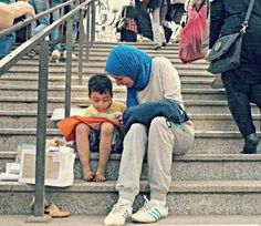 3.) A young Egyptian girl helps a street vendor's child learn how to read.