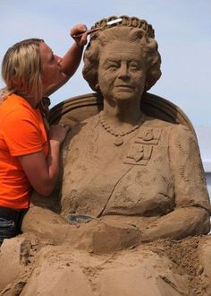 Sand sculpture artist Nicola Wood completes a sand sculpture she has created of Queen Elizabeth II for the annual Weston Super-Mare Sculpture Festival in England.