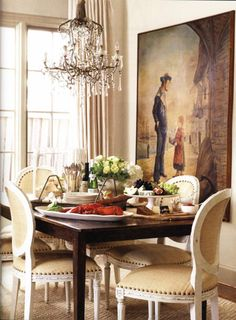Elegant, european style dining area with chandelier and beautiful painting on the wall. The french door (or window, I'm not sure) is lovely.