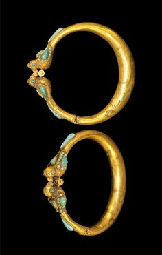 ISLAMIC GOLD AND TURQUOISE BIRD BRACELET Circa 12th century AD or later. A medieval Islamic sheet-gold expanding bracelet formed as a c-shaped band with a hinged upper section; the band with terminals formed as an opposed pair of birds with turquoise details in cells (eyes, wings, tail). Gold and turquois