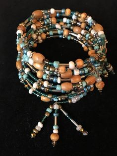 This bracelet has various beads such as seed beads, wood beads, glass beads, etc. It is made from memory wire. It is also accented with seed bead tassels.
