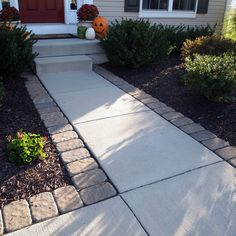 Adding pavers around a standard concrete walkway can give your entrance a little something extra. And soo much less expensive than redoing the whole thing. This would look great for our front walk way!