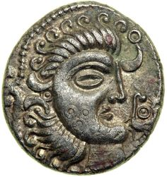 """Celtic Tattooed Face Coin from Jersey, Armorica, Struck Circa 80-50 BCThe obverse of this coin shows a lunate aka """"moon"""" head with a triadic tattoo on his cheek, a """"horn"""" above with a """"bent nail"""" and a pellet in an annulet in the lower right. The..."""