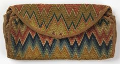 """Envelope-shaped purse with flame stitch embroidery in wool in shades of red, blue, and brown. Lined with rose colored linen.    This purse is medium: wool on linen ground technique: brick stitch embroidery on plain weave. Its dimensions are: H x W: 11 x 22 cm (4 5/16 x 8 11/16 in.).    This purse is from United States and dated """"18th century""""."""