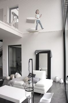 Architecture House Loft The net above the living room in this modern home creates a play space for kids, and a relaxing spot for grownups.