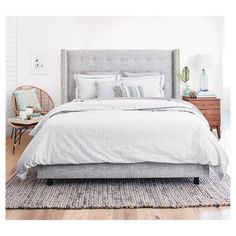 Upgrade where you sleep. A blend of chic and cozy, this upholstered bed is decked out in smart details like nailheads and button-tufts, both finished by hand. A contemporary wingback silhouette completes the look of comfy sophistication.