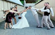 Kissing bride and groom with bridesmaids and groomsmen pulling them