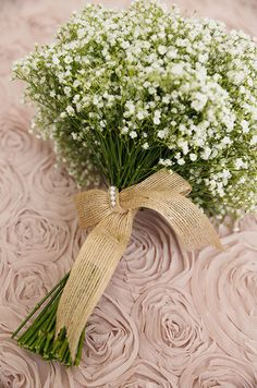 Fabric rosettes serve as the backdrop for a bundle of baby's breath.
