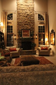 stone fireplace with flanked windows and ceiling to floor curtains.  Looks almost identical to my mom's living room, except for the fireplace which she wants.