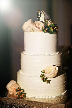 A traditional, hree-tiered white wedding cake with flowers | Brides.com
