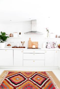 White kitchen with bright patterned rug, plants, flowers, wood cutting boards, candles, and gold light fixtures