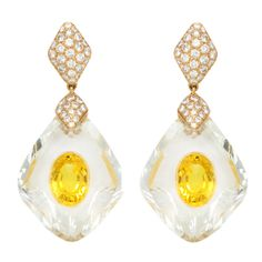 CARTIER A pair of stylish chandelier earrings set with two oval sapphires, within a rock crystal base. Set on 18 karat gold. Signed Cartier paris with Serial Numbers. Circa 1970s