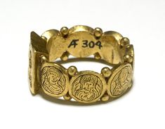 Gold signet-ring (Right Side), 5th c., composed of a square bezel with angled sides and a hoop constructed of seven small medallions between each of which are two small granules. This is certainly an example of a marriage ring and may have been one of a pair. Its comparatively large size suggests that it was either made for the husband or to be worn on the forefinger or thumb. External diameter: 26 mm.