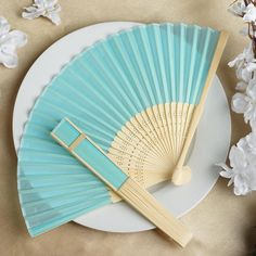 Asian Silk Folding Fans - Turquoise | eFavorMart / Add a classical Asian touch to your wedding, or a special event by presenting your esteemed guests with this special souvenir. Our stylish silk wedding hand fan is intricately handcrafted with a bamboo structure. The framing and spines are crafted from hand-picked bamboo and durably glued with a seamless cut piece of silk to fashion this immaculate magnum opus. Give these swish fans to your respected guests and let them create the lasting…